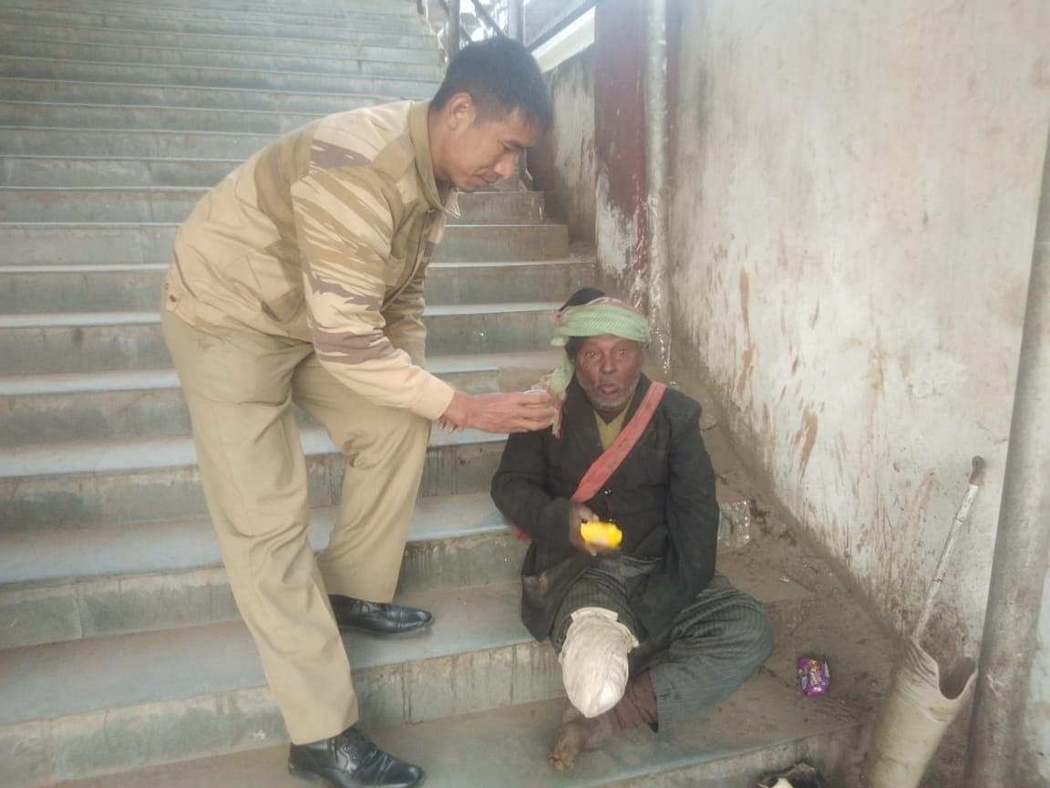 A policeman offering snacks to a homeless person in Dimapur, Nagaland