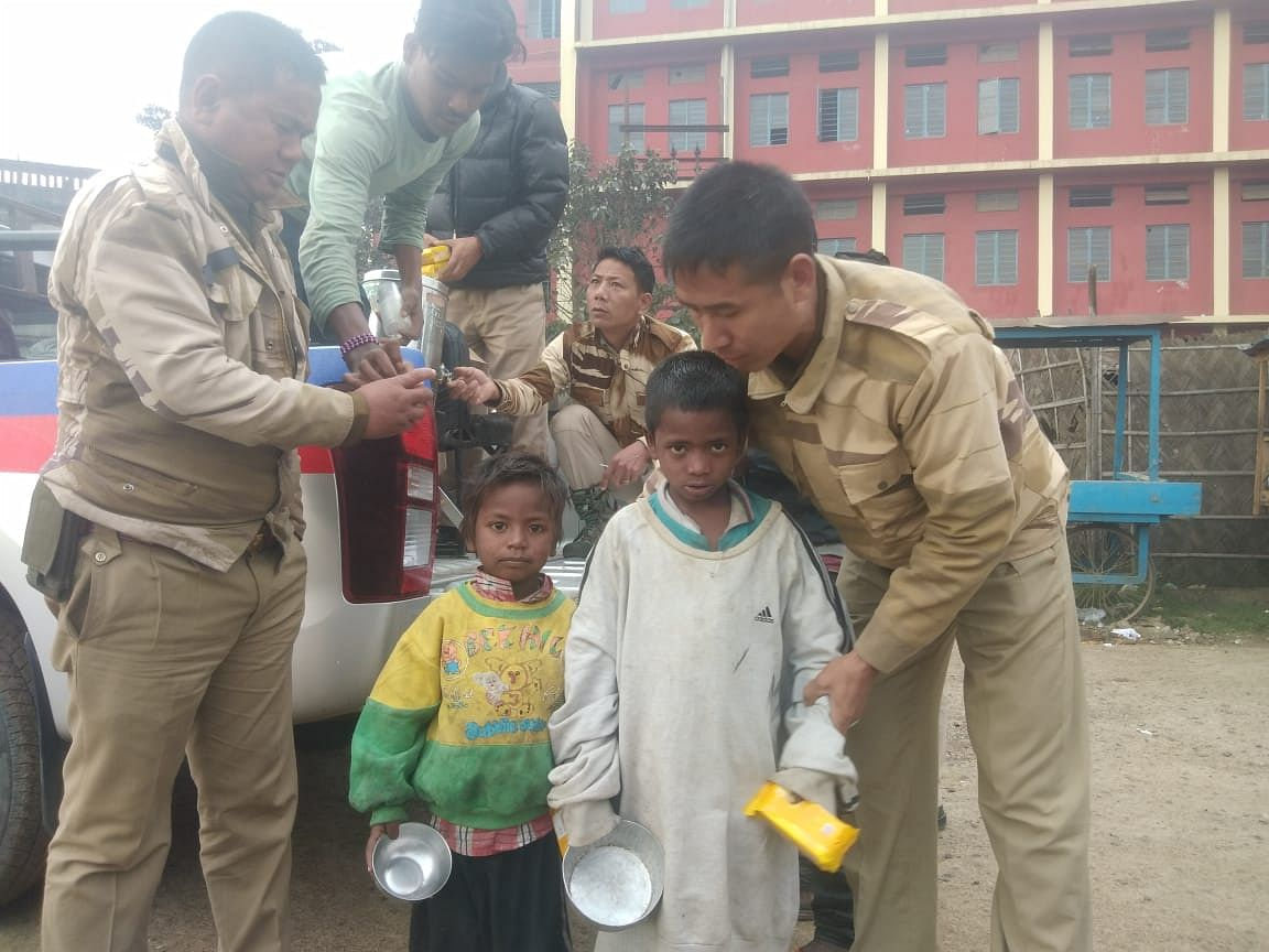 Street children posing with policemen after they were offered snacks in Dimapur, Nagaland