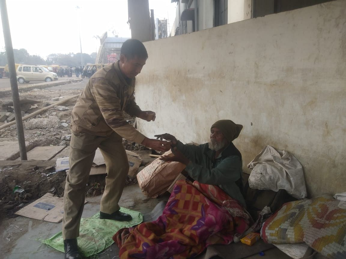Another beggar being offered a hot cup of tea by a policeman in Dimapur, Nagaland