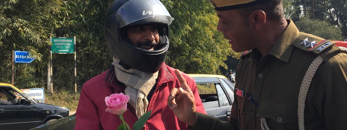 Meghalaya police giving a pink rose to a traffic violater