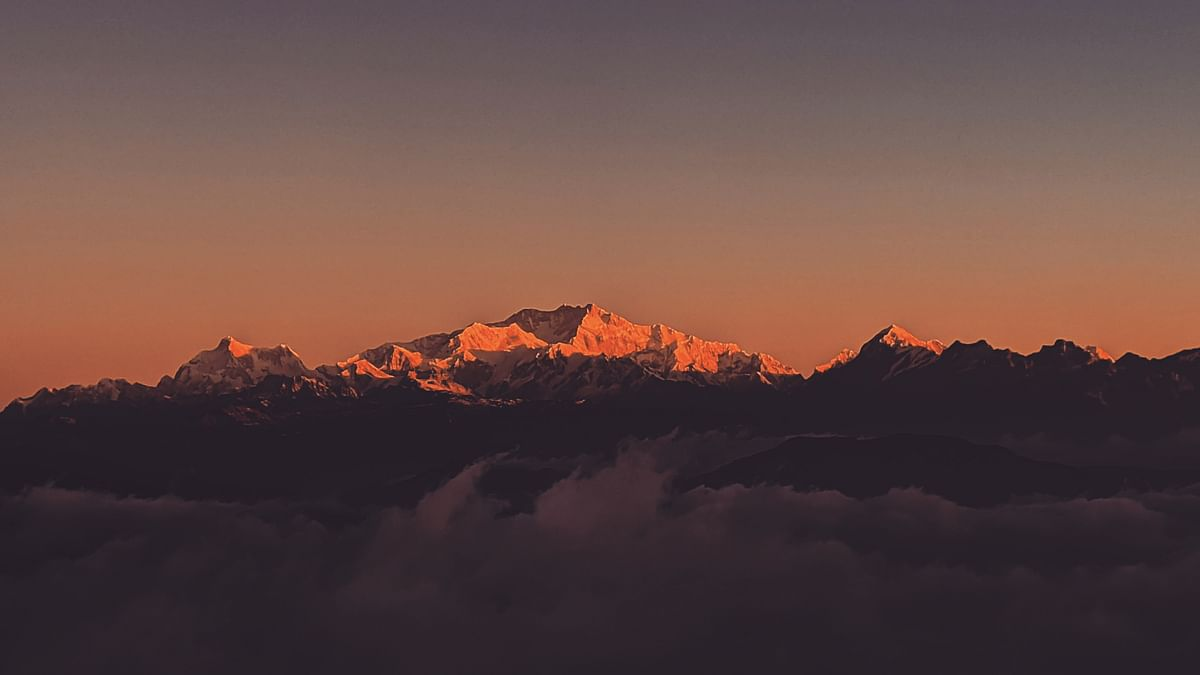 View of the sunrise from Sandakphu – 'Sleeping Buddha' rises and shines along with Mount Everest range of Makalu, Lhotse and Mount Everest