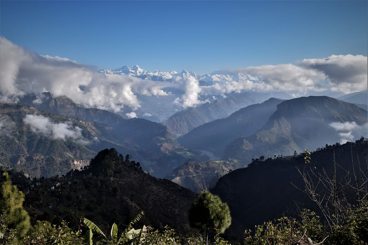 The snowclad Api Himal range of the High Himalayas in the background, with the Mahakali River flowing through richly forested mountains – as seen from the mountains of Dadeldhura, Nepal