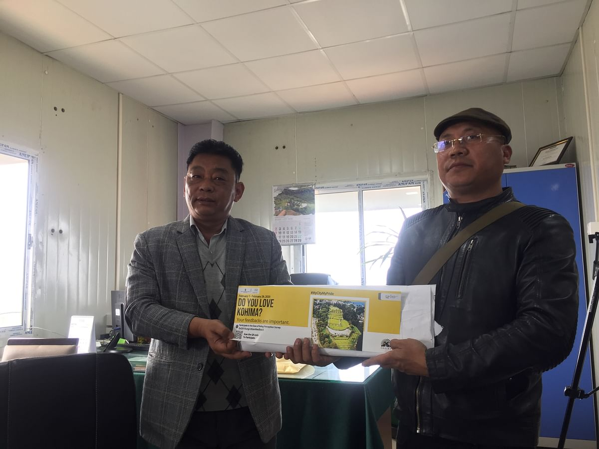 CEO Kovi Meyase (left) handing over Kohima Smart City Car stickers to the general secretary of Kohima Buses Union at his office on Thursday