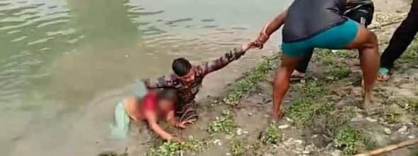 Army personnel saving a woman from drowning in Nausatra Nallah in Barpeta district of Assam
