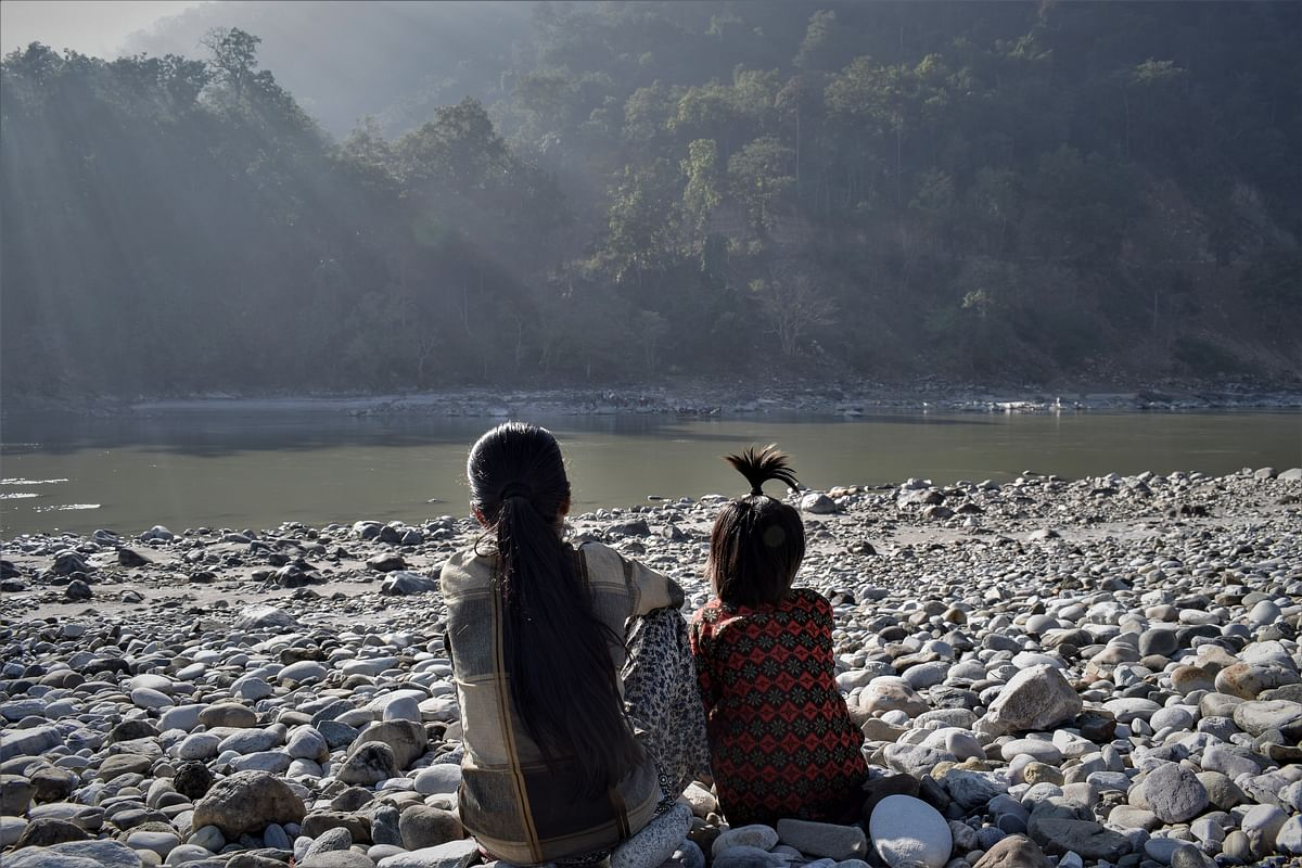 Two girls look across the Mahakali at India