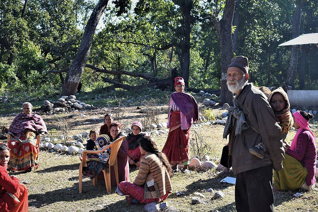 A grandfather helps out as a babysitter while a Women's Empowerment Committee meeting gets underway in a village in the Mahakali basin