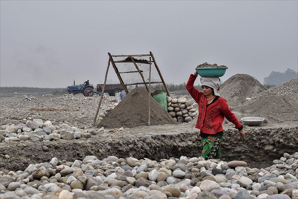Women from riverside villages work as daily wage labourers, quarrying stones and sieving sand from the riverbed
