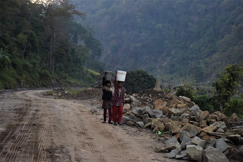 Women and girls spend hours every day, clambering down steep hillsides to fetch water from the river, and then walking up with laden vessels