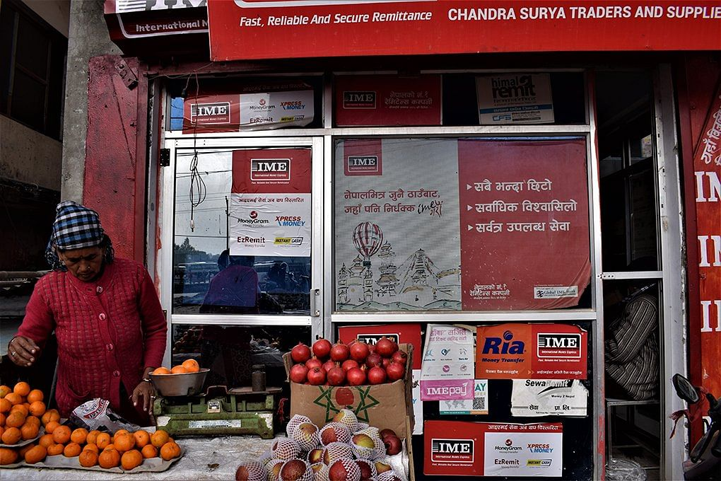 A woman runs a fruit stall in front of an advertisement for a remittance delivery firm