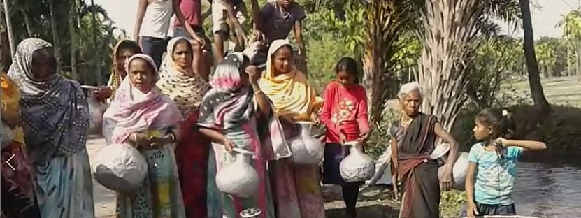 Women from Deusunga village fetching water from bore well made in middle of a flowing stream