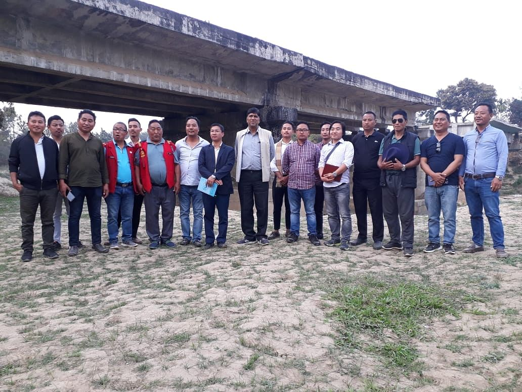 A team of experts and officials from the government and the village council pose for a photograph  after conducting a survey of the bridge in Nagaland's Dimapur district on Friday