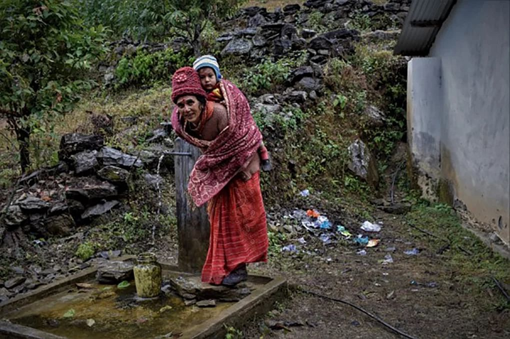Nanda Daga stands at the tap that provides clean drinking water to the local school