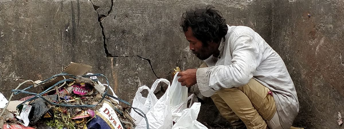 Person eating food from the dumped packets in a garbage bin