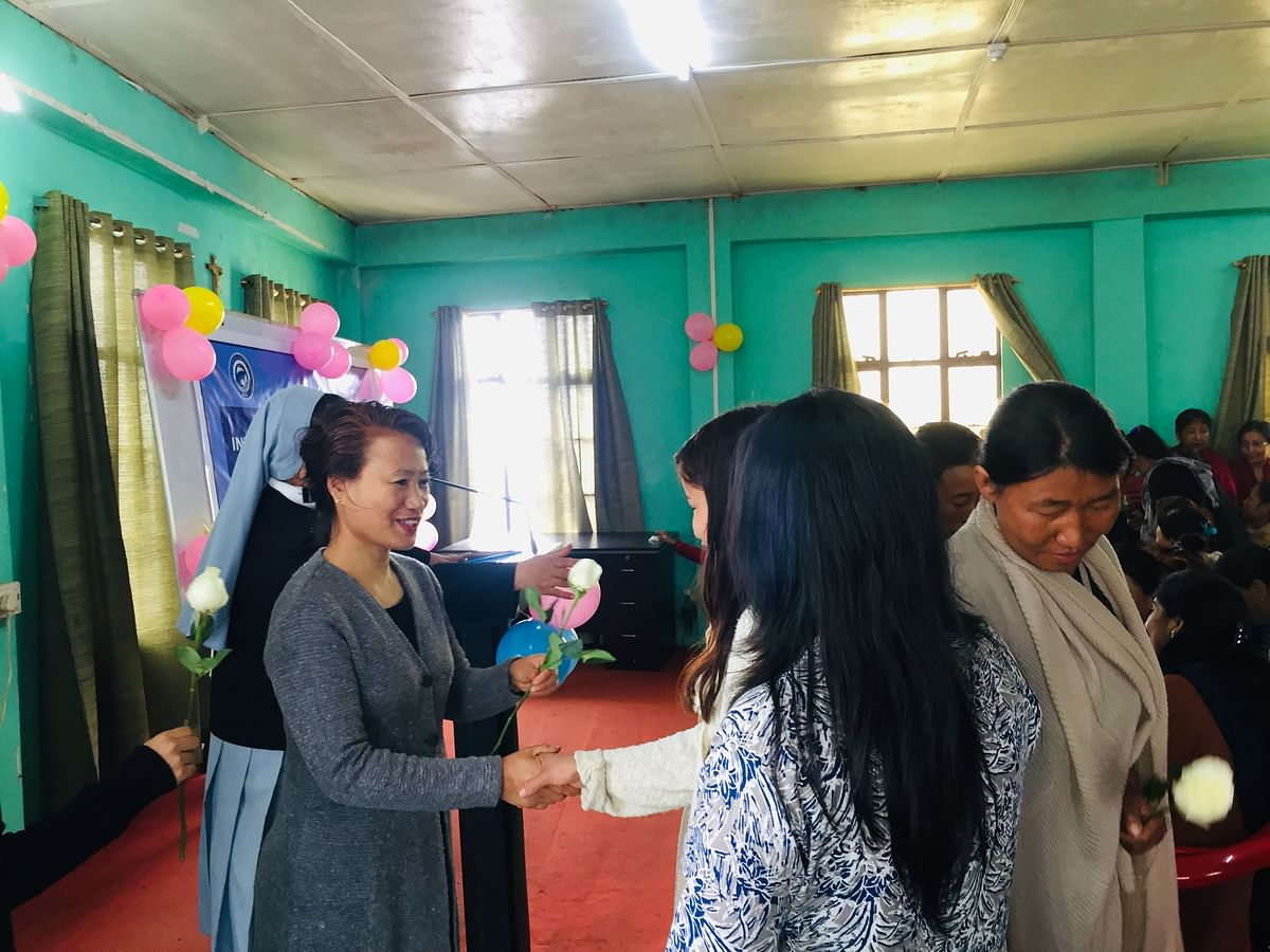 Assistant Labour Commissioner, Avile Vitso, handing over white roses to the domestic workers.