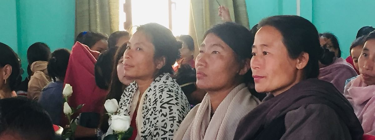 Domestic workers hold their white roses as they attend a ceremony in Kohima ahead of International Women's Day on Saturday