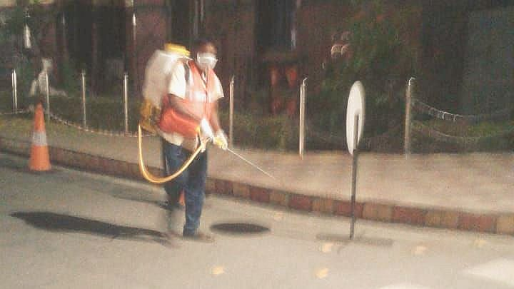 A sanitation worker of Guwahati Municipal Corporation spraying antibacterial on streets of the city