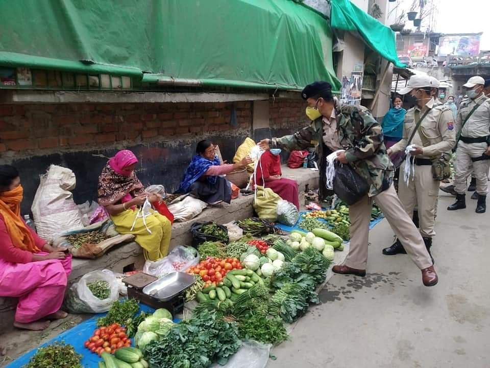 Police personnel distributing stitched face masks to women vendors