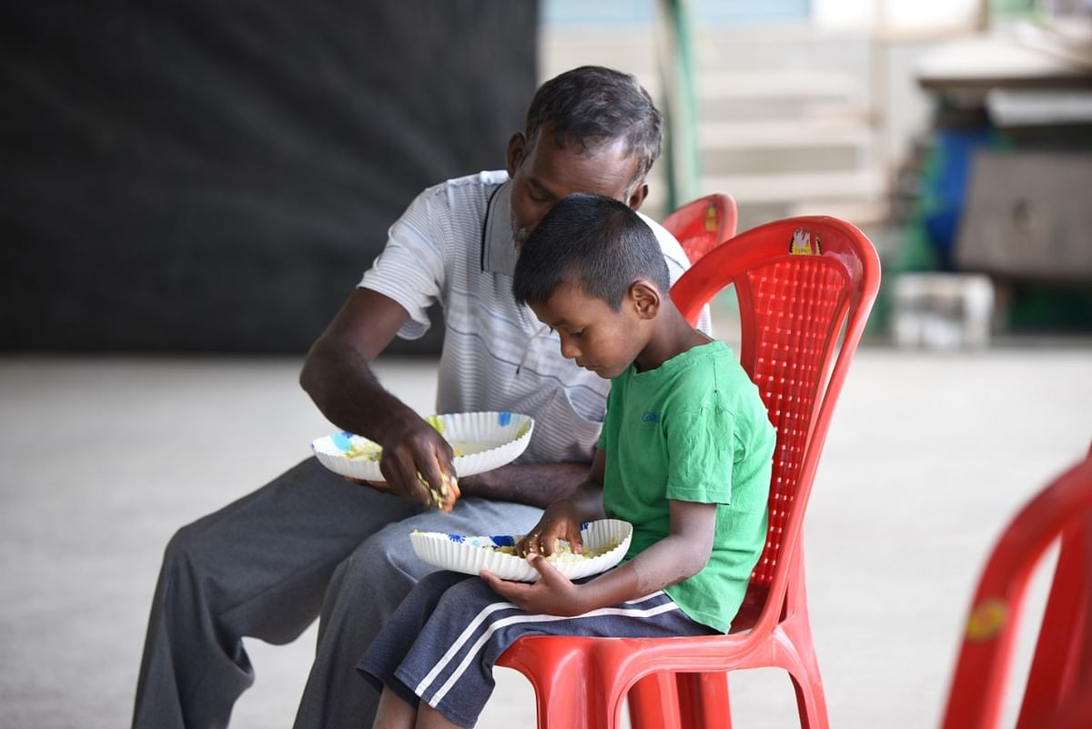 A father and son seen enjoying  food served  by the district administration and Mokokchung Town Baptist Church