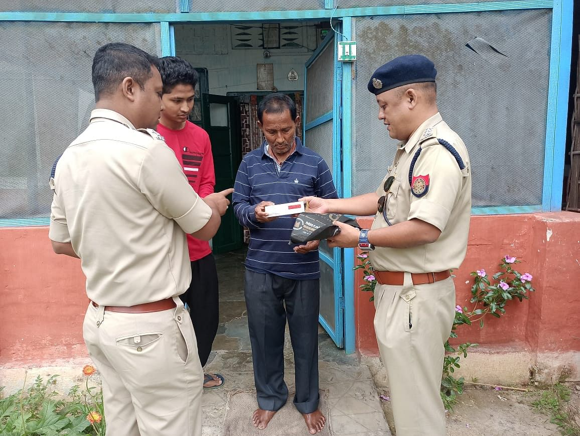 Police officers handing over medicines to a needy person in Assam's Charaideo district amid the national lockdown