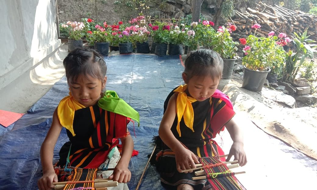 Karizia Phimu and Athedziia Kape, both six-year-old girls from Maopungdong village in Manipur's Senapati district, trying their hands at traditional loin loom weaving