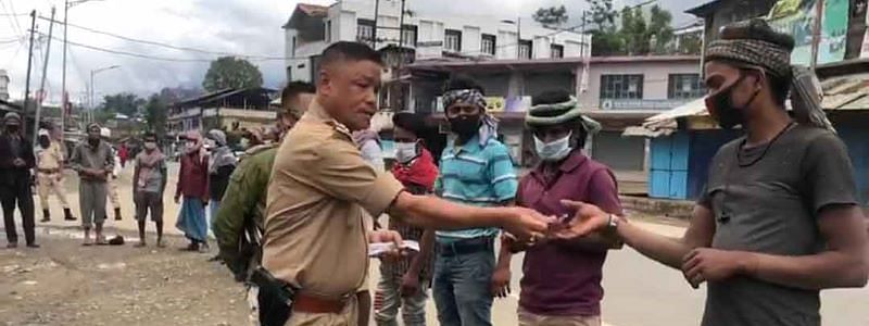Inspector Khogen distributing face masks and financial aid to migrant workers in Kangpokpi district in Manipur