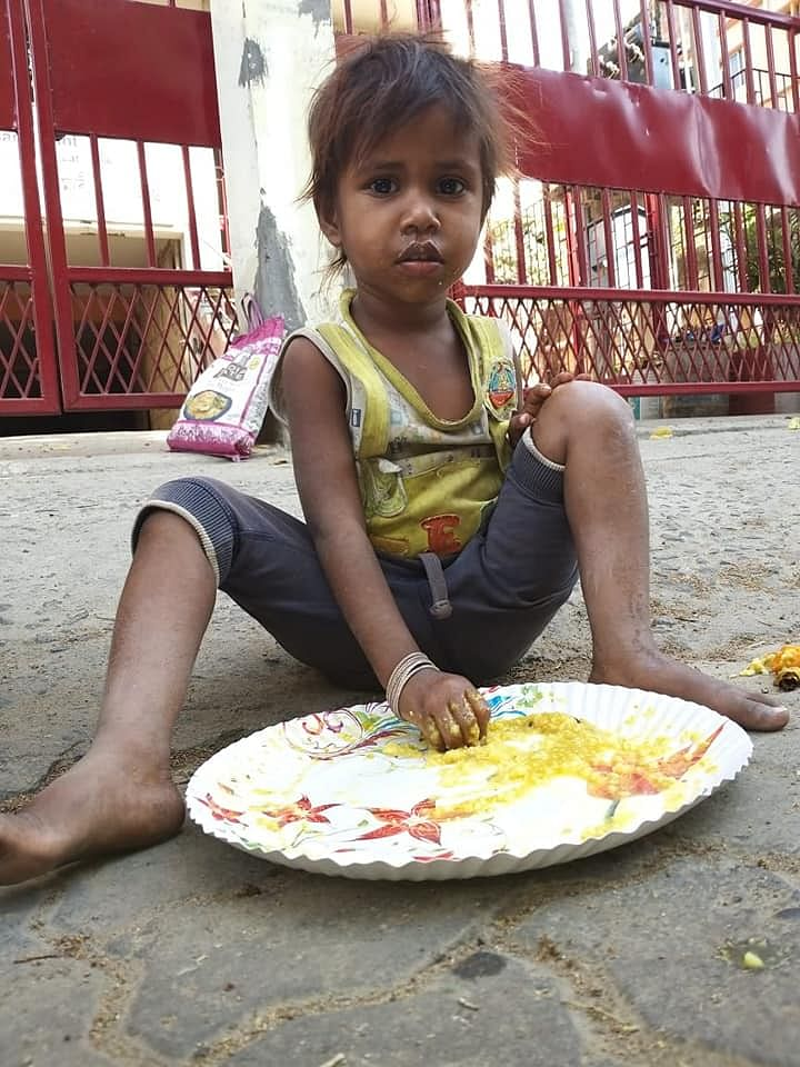 A hungry child having food served at a '<i>langar'</i>