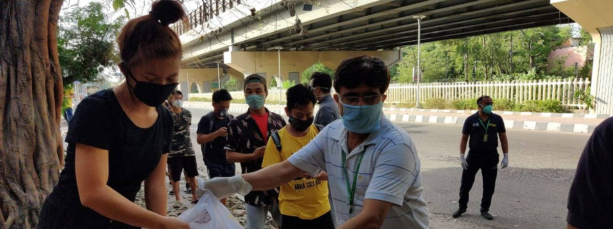 Students receiving relief food package from Manipur state official in Delhi