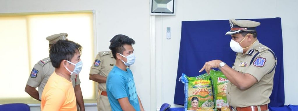 Rachakonda police commissioner Mahesh Bhagwat interacting with the two youths from Manipur and handing over bags of rice, pulses and other essential items