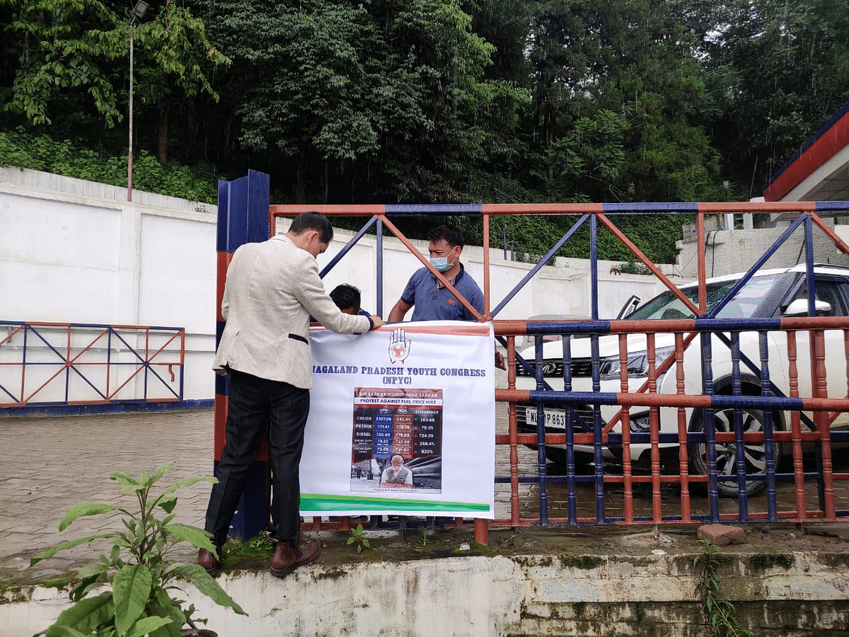 Congress workers putting up a poster at a petrol pump in Kohima