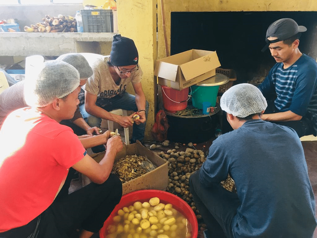 Some of the youth volunteers are seen peeling potatoes