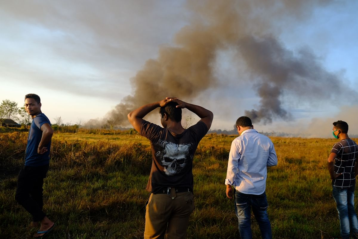 Locals look from a distance with exasperation as the fire and the spill damages their soil and air