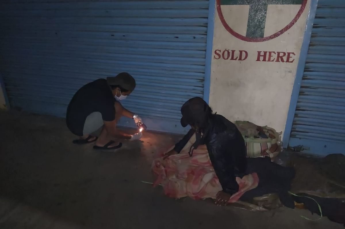 A member of Dimapur 24/7 lighting up a mosquito repellant for a homeless person on the streets of Dimapur