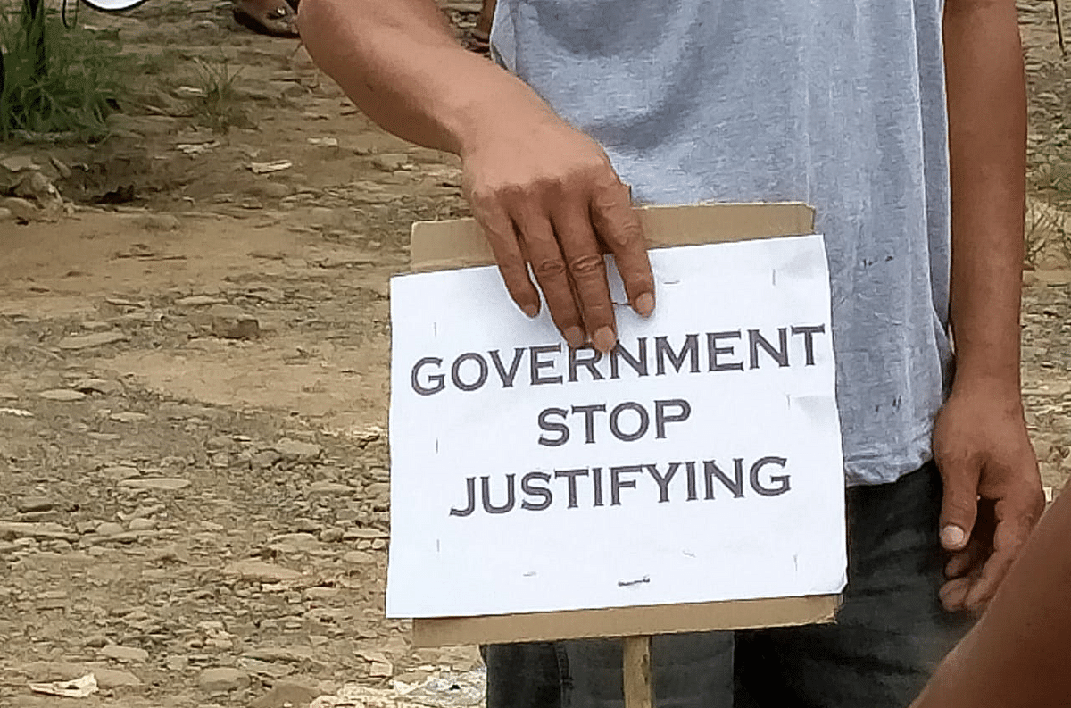 A protester holds a placard which reads 'Government stop justifying'