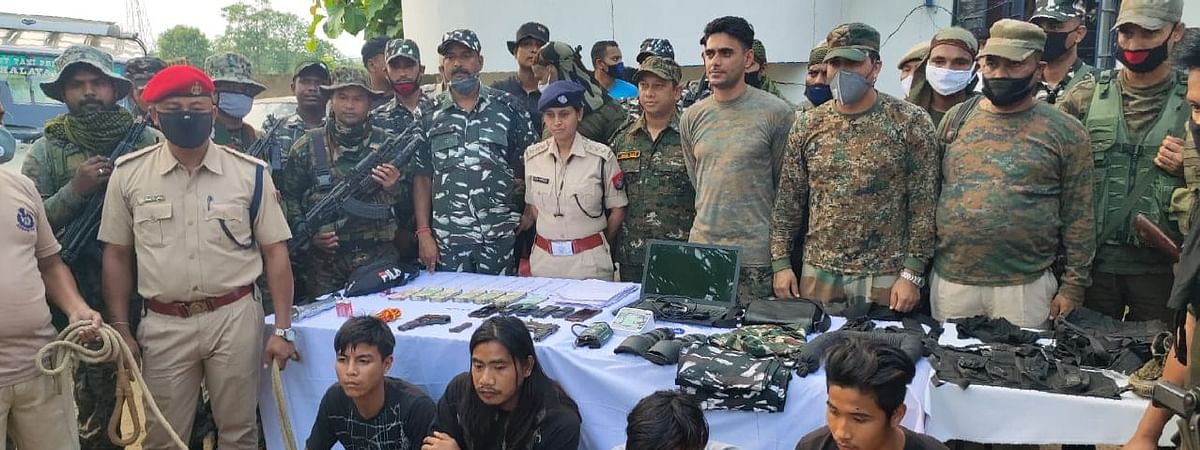 Security forces along with the arrested members of the militant outfit