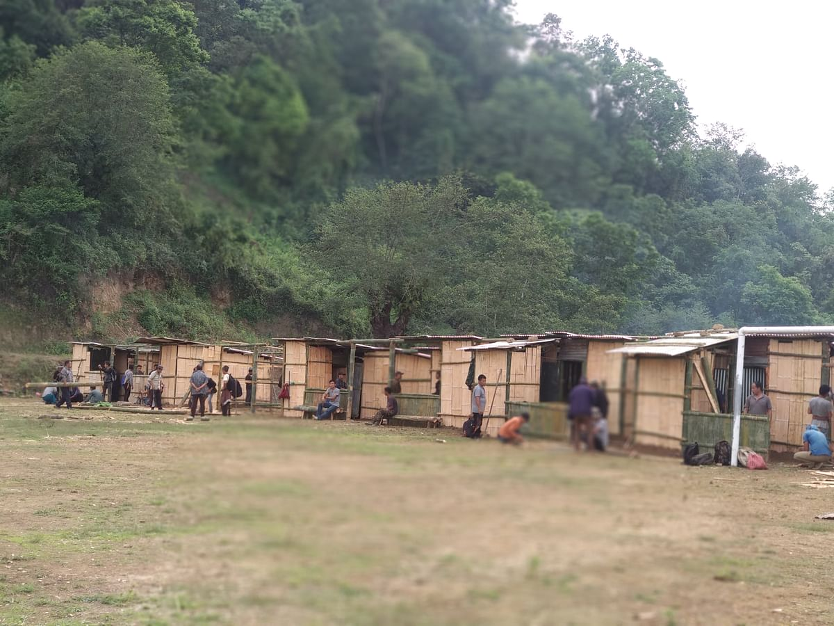A photo of villagers seen building bamboo huts for returnees