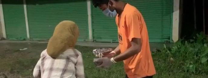 Cyclist Rohan Philem offering cooked food to a homeless woman in Imphal