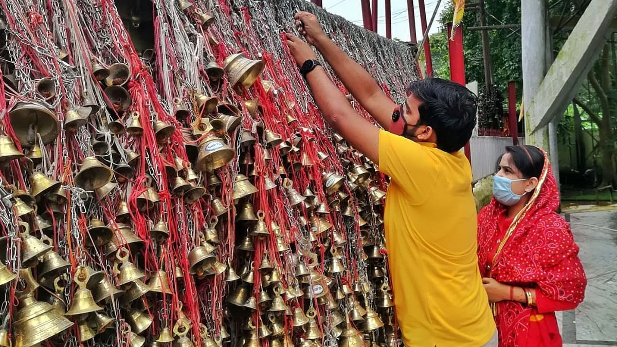 Bells of various sizes are hung on the tree branches and the walls by devotees