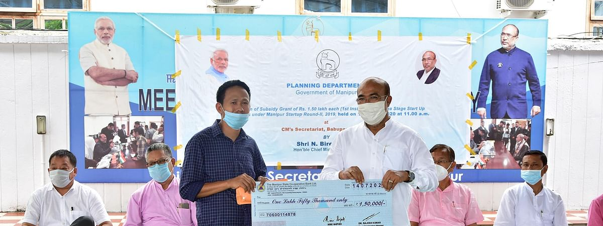 CM N Biren Singh handing over a cheque of Rs 1.50 lakh to a beneficiary