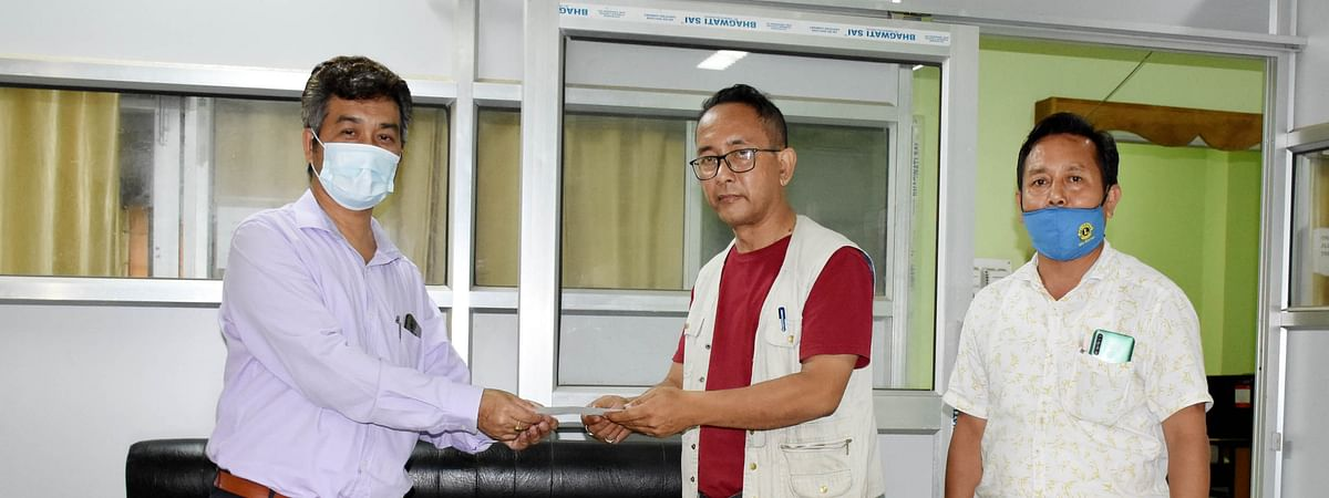 'Imphal Times' editor Rinku Khumukcham (middle) receiving financial aid on Wednesday