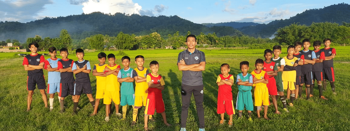 Lironthung Lotha (centre) along with his students at a picturesque football ground in Nagaland's Wokha district