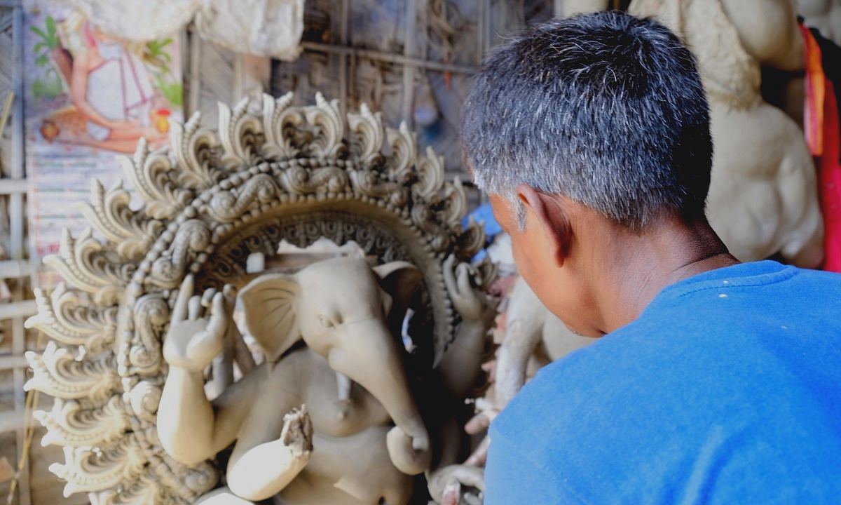 An idol-maker giving final touches to a year-old Ganesh idol in Guwahati