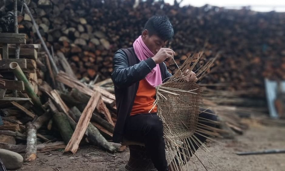 Artisan Robert Rovei making traditional bamboo basket in Senapati district