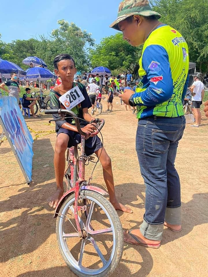 The image of a young barefoot cyclist from Cambodia