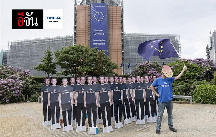ผู้ประท้วงถือธงสหภาพยุโรป ยืนข้างหุ่นสแตนดี้กองทัพซักเคอร์เบิร์กขนาดเท่าตัวจริง