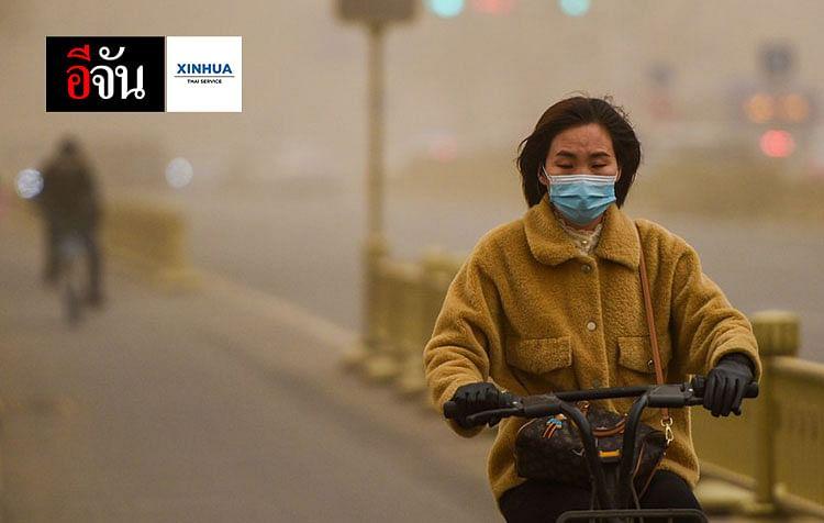 หญิงสวมหน้ากากอนามัยขี่จักรยานไฟฟ้าท่ามกลางฝุ่นละออง ที่ปกคลุมเมืองฮูฮอต เขตปกครองตนเองมองโกเลีย ทางตอนเหนือของจีน