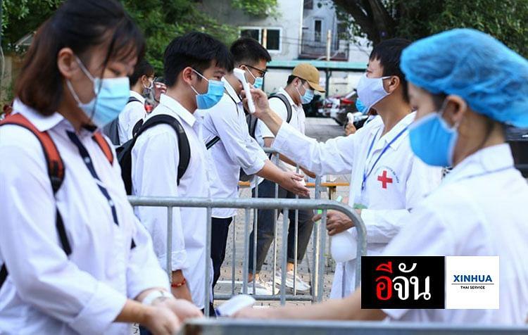 กเรียนรับการตรวจวัดอุณหภูมิร่างกายและทำความสะอาดมือก่อนเข้าห้องสอบที่โรงเรียนแห่งหนึ่งในกรุงฮานอย