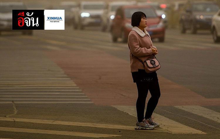 หญิงสาวยืนท่ามกลางฝุ่นละอองที่ปกคลุมเมืองฮูฮอต เขตปกครองตนเองมองโกเลีย ทางตอนเหนือของจีน