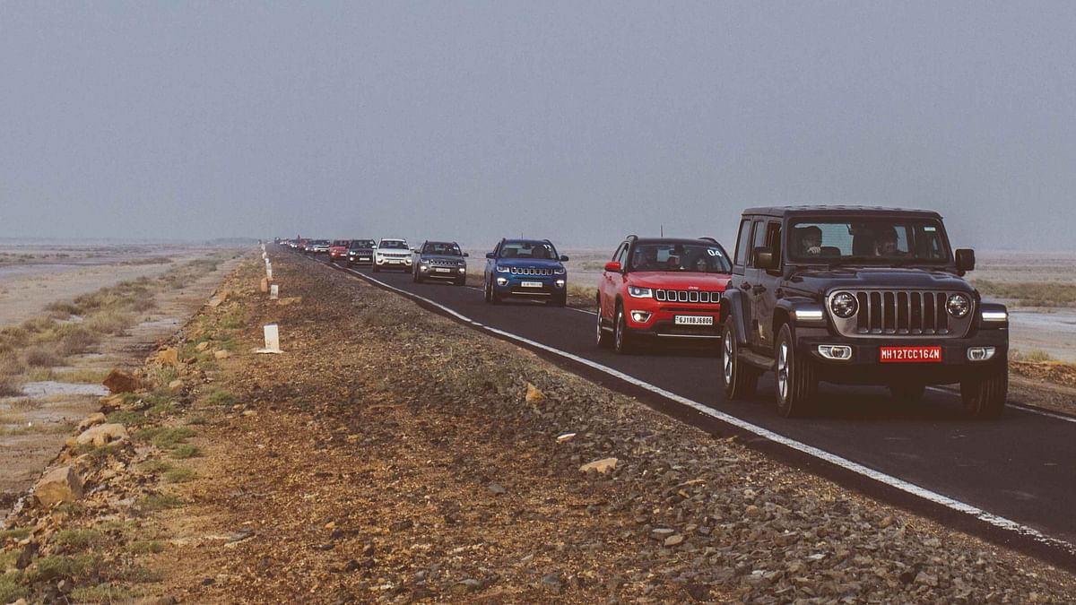 Trail of Jeep cars moving across like an army of ants with the Rann of Kutch spread endlessly on either sides