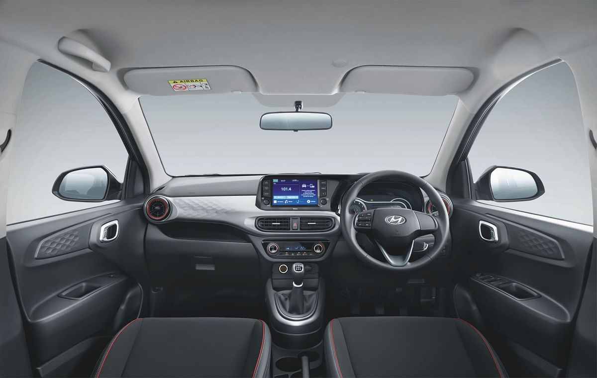 All-black leather interior stitched in red, a digital speedometer, a touchscreen infotainment system with smartphone connectivity