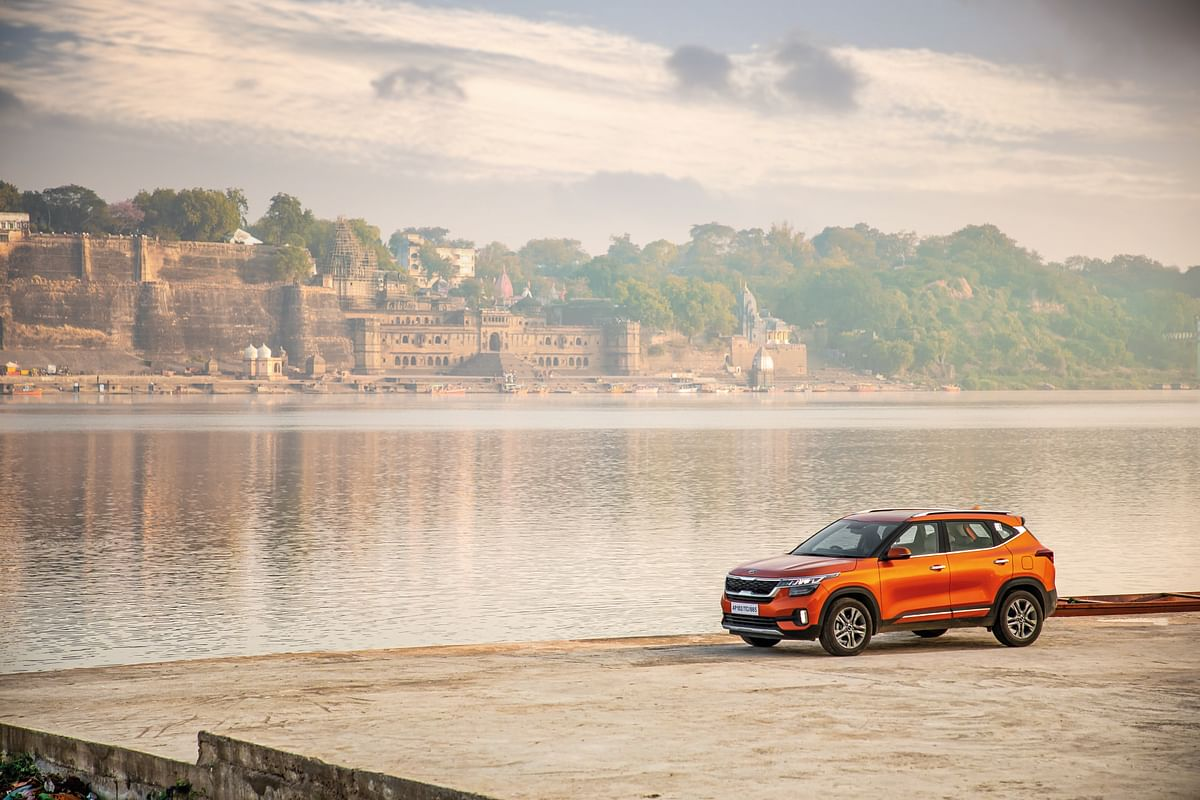 The Kia Seltos by the side of the river Narmada with the Maheshwar fort in the background.